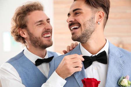 Foto de Happy newlywed gay couple with flower at home - Imagen libre de derechos
