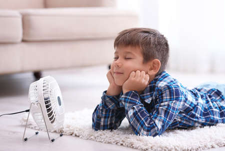 Foto de Little boy refreshing from heat in front of small fan at home - Imagen libre de derechos