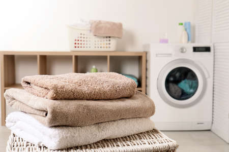 Foto de Stack of clean soft towels on basket in laundry room. Space for text - Imagen libre de derechos