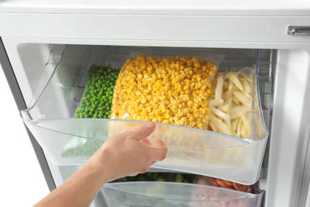 Photo pour Woman opening refrigerator drawer with frozen vegetables, closeup - image libre de droit