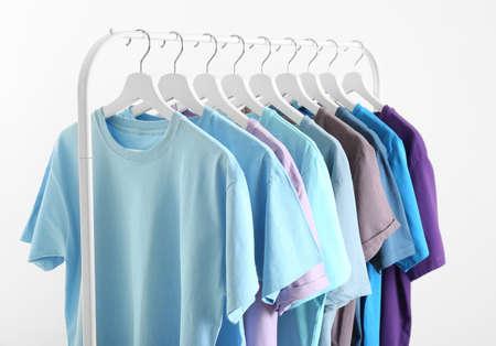 Foto de Men's clothes hanging on wardrobe rack against white background - Imagen libre de derechos