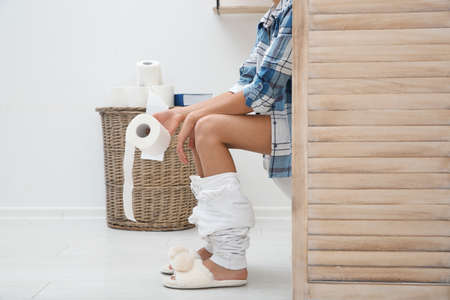 Foto de Woman with toilet paper roll behind folding screen in bathroom - Imagen libre de derechos