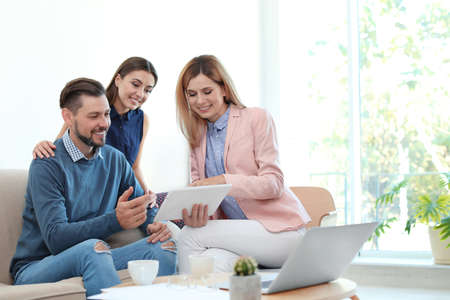 Photo for Female real estate agent working with couple in office - Royalty Free Image