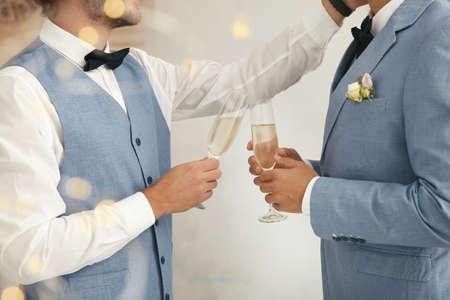 Foto de Newlywed gay couple with glasses of champagne at home, closeup - Imagen libre de derechos