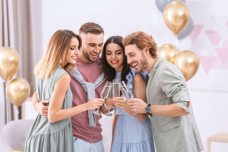 Photo pour Happy friends with champagne in glasses at home - image libre de droit