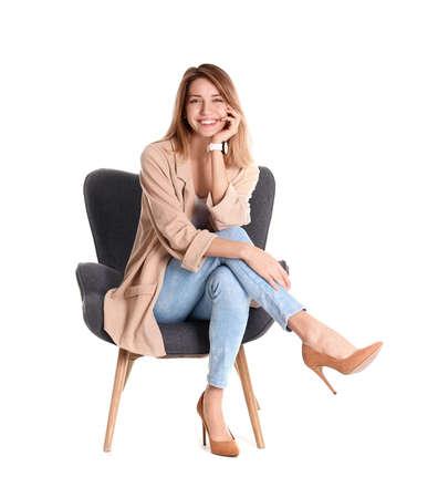 Foto de Young woman sitting in armchair on white background - Imagen libre de derechos