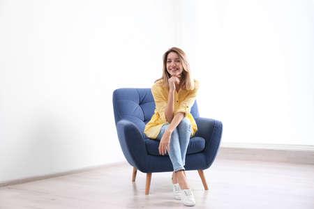 Foto de Young woman sitting in armchair at home - Imagen libre de derechos