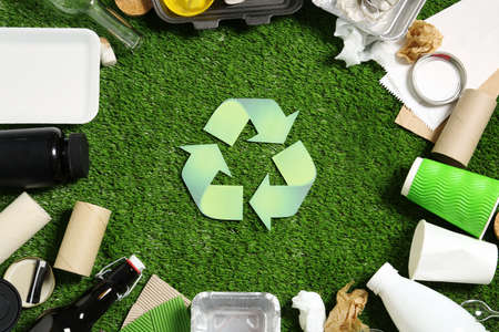 Foto de Recycling symbol and different garbage on synthetic turf - Imagen libre de derechos