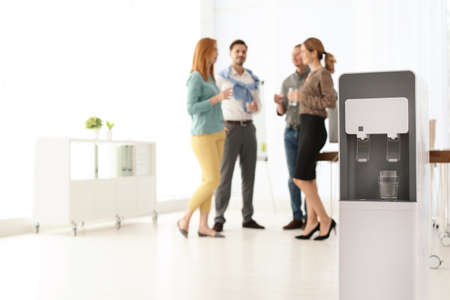 Photo for Modern water cooler with glass and blurred office employees on background. Space for text - Royalty Free Image