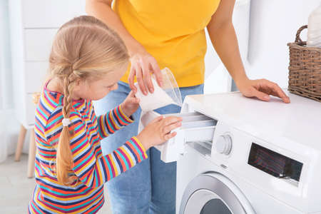 Foto de Little girl helping her mother to do laundry at home - Imagen libre de derechos