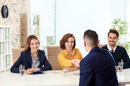 Photo for Human resources manager shaking hands with applicant before job interview in office - Royalty Free Image