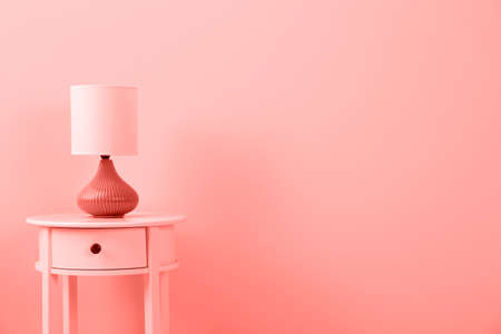 Photo pour Stylish lamp on table against color wall, space for text. Design with living coral color - image libre de droit