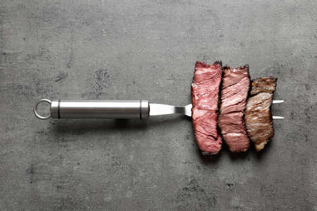 Photo pour Fork with pieces of delicious barbecued meat on gray background, top view - image libre de droit