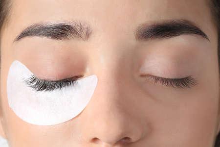 Photo pour Young woman undergoing eyelashes extensions procedure, closeup - image libre de droit