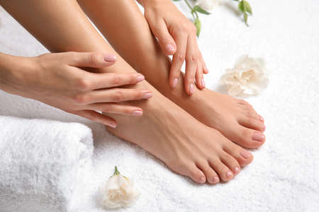 Foto de Woman touching her smooth feet on white towel, closeup. Spa treatment - Imagen libre de derechos