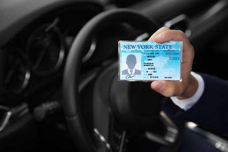 Photo pour Man holding driving license in car, closeup. Space for text - image libre de droit