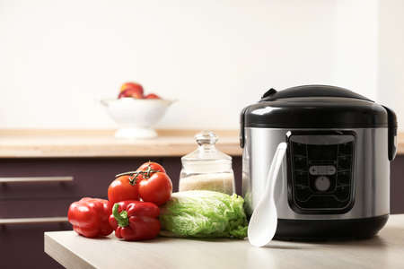 Foto per Modern multi cooker and products on table in kitchen. Space for text - Immagine Royalty Free