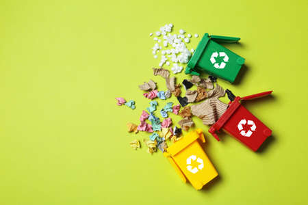 Foto de Trash bins and different garbage on color background, top view with space for text. Waste recycling concept - Imagen libre de derechos