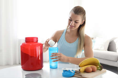 Photo for Young woman preparing protein shake at table in room - Royalty Free Image