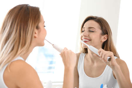 Photo for Young beautiful woman with toothbrush near mirror in bathroom. Personal hygiene - Royalty Free Image