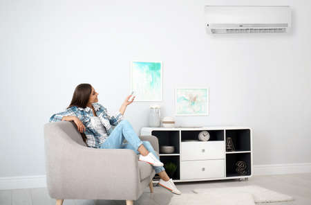 Foto de Young woman turning on air conditioner at home - Imagen libre de derechos