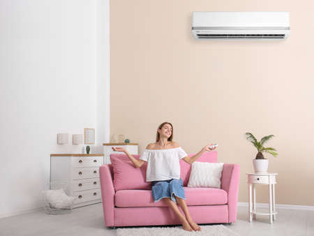 Photo pour Young woman relaxing near air conditioner at home - image libre de droit