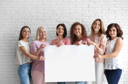 Foto de Women wearing silk ribbons holding poster with space for text against brick wall. Breast cancer awareness concept - Imagen libre de derechos