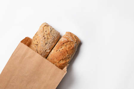 Foto de Paper bag with bread loaves on white background, top view. Space for text - Imagen libre de derechos