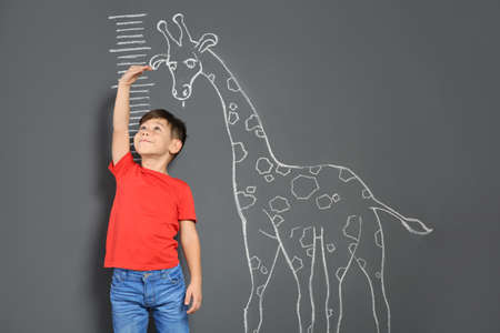 Foto de Cute little child measuring height near chalk giraffe drawing on grey background - Imagen libre de derechos