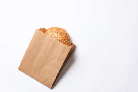 Photo for Paper bag with sesame bun on white background, top view. Space for text - Royalty Free Image