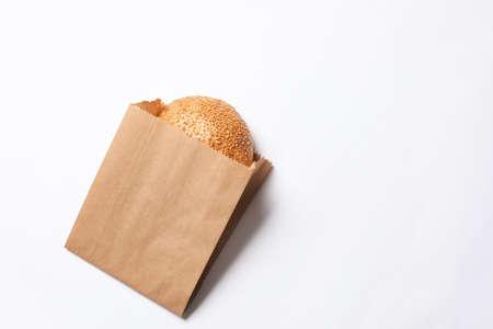 Foto de Paper bag with sesame bun on white background, top view. Space for text - Imagen libre de derechos