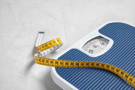Foto de Scales and measuring tape on light background with space for text. Weight loss - Imagen libre de derechos