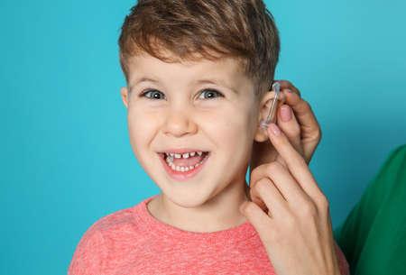 Foto de Young woman adjusting little son's hearing aid on color background, closeup - Imagen libre de derechos