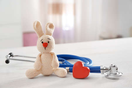 Photo pour Toy bunny, stethoscope and heart on table indoors, space for text. Children's doctor - image libre de droit