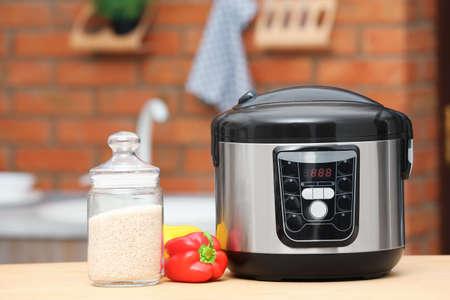 Foto de Modern electric multi cooker, jar of rice and peppers on table in kitchen - Imagen libre de derechos