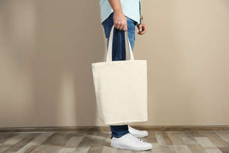 Photo pour Young man holding textile bag against color wall, closeup. Mockup for design - image libre de droit