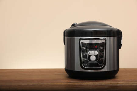 Photo pour Modern electric multi cooker on table against color background. Space for text - image libre de droit