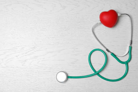 Foto de Stethoscope with red heart on white wooden background, flat lay. Space for text - Imagen libre de derechos