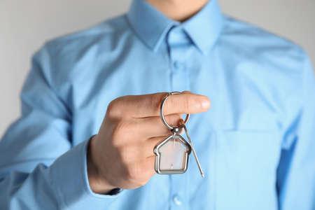 Photo pour Young man holding house key with trinket, closeup - image libre de droit