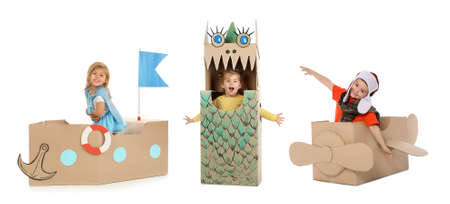 Little cute children playing with cardboard boxes on white background. Handmade toys and costume