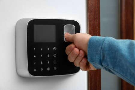 Foto de Man scanning fingerprint on alarm system indoors, closeup - Imagen libre de derechos