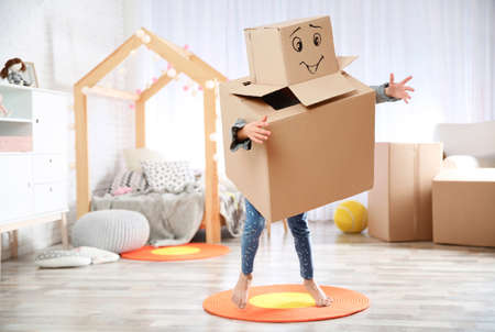 Foto de Cute little child wearing cardboard costume in bedroom - Imagen libre de derechos