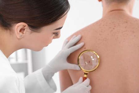 Photo pour Dermatologist examining patient with magnifying glass in clinic, closeup view - image libre de droit