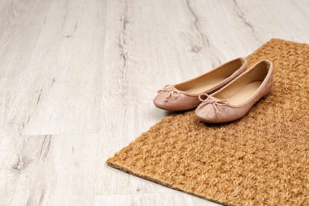 Photo for New clean doormat with shoes on floor. Space for text - Royalty Free Image