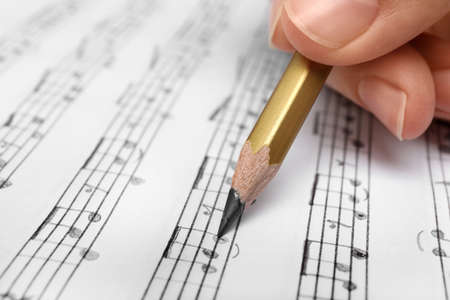 Photo pour Woman writing music notes on sheet with pencil, closeup - image libre de droit