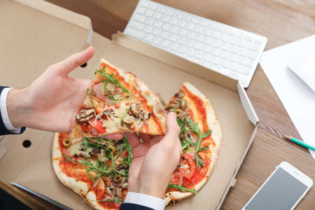 Photo for Office employee having pizza for lunch at workplace, closeup. Food delivery - Royalty Free Image