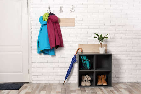 Photo pour Stylish hallway interior with shoe rack and hanging clothes on brick wall - image libre de droit