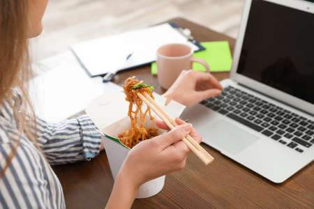 Photo for Office employee using laptop while having noodles for lunch at workplace, closeup. Food delivery - Royalty Free Image