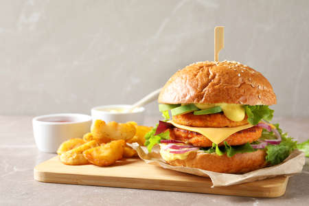 Foto per Board with double vegetarian burger and fried potatoes on table - Immagine Royalty Free