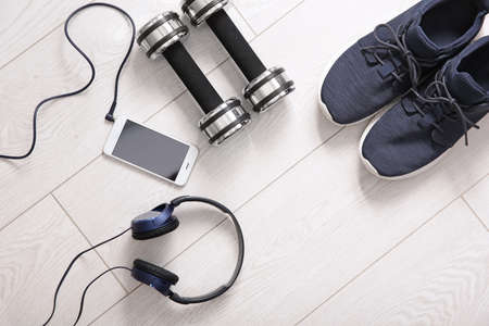 Flat lay composition with sneakers, headphones, mobile phone and dumbbells on wooden background